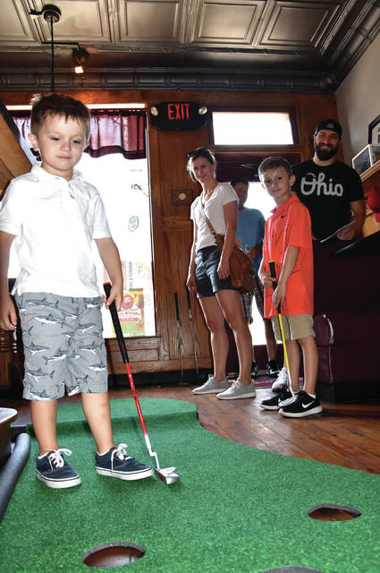 "Cody Willoughby | Troy Daily News Ian Kucharski, 4, of Dayton scores a hole-in two, as Audra, Eliot, and Kevin Kucharski look on, during ""Putt-Putt Through Tipp"" on Friday in Tipp City."