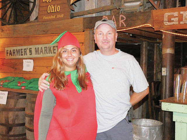 Rachel Hensley | For AIM Media Midwest Jennifer and Jeffrey Gill take a break from the festivities at the Home Grown Tomato Fest, held Saturday in Tipp City's Canal Lock Park. Jennifer was the mascot; Jeffrey works for TIP Top Canning Co., which sponsored the festival.