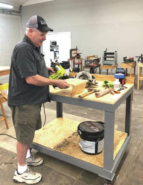 Provided photo Habitat for Humanity volunteer David Kinninger works on a woodworking project at one of the newly fabricated tables built and donated by Hobart.