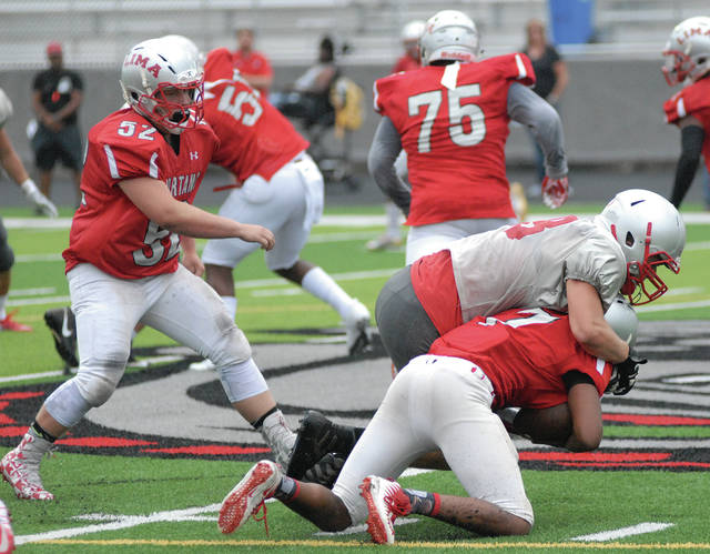 David Fong | Miami Valley Sunday News Troy defensive lineman Zach Niswonger (top) records a quarterback Friday in Troy's scrimmage against Lima Senior at Spartan Stadium.
