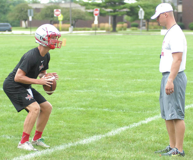 David Fong | Troy Daily News Troy quarterback Brayden Siler goes through a drill under the watchful eye of offensive coordinator Tyler Wright earlier this week.