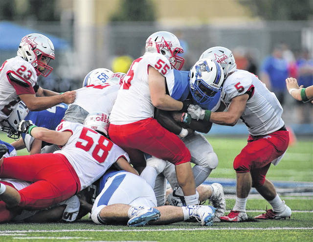 Lee Woolery/Troy Daily News Troy's Sam Jackson (5), Colby Harris (55) and Zach Niswonger (58) stop a Xenia ballcarrier Friday night in Xenia. The Trojans finished off a 21-14 victory Saturday morning in a lightning-delayed game.