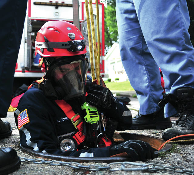 Piqua firefighter Nick Schmitz is lowered in to a storm sewer on Linden Ave. on Thursday morning. He and Firefighter Tony Stutter were sent to recover a robotic crawler belonging to the Underground Utilities Department. The machine overturned some 200 yards from the manhole in a 48 inch drain pipe and firefighters went into the storm sewer to recover the machine. Once into the storm drain system, firefighters completed the job in less than 25 minutes.