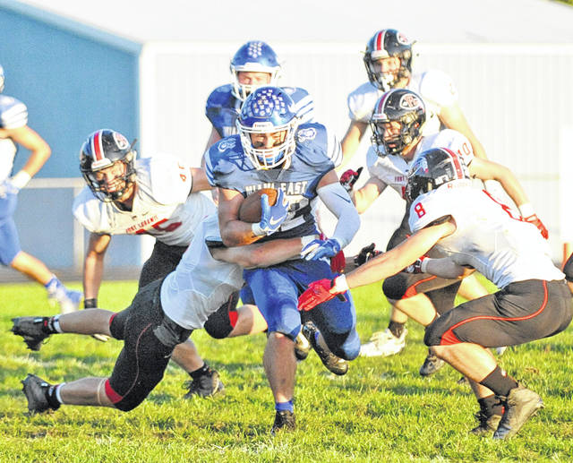 Josh Brown|Troy Daily News file Miami East's Vincent Villella carries the football through Fort Loramie's defense Friday.