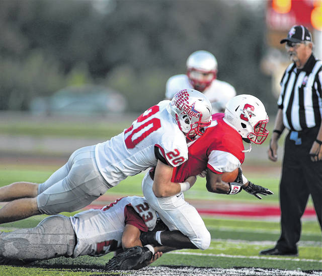 Lee Woolery | Troy Daily News Troy linebackers Blake Burton (20) and Shane Shoop (23) make a tackle against Stebbins earlier this season.