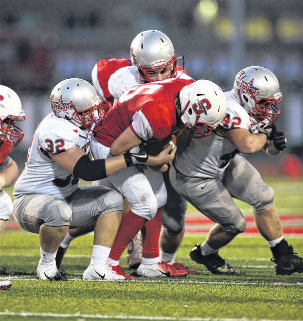 Lee Woolery | Troy Daily News Troy's Garrett Jones (32) and Austin Blair (42) swarm to the ball Friday against Stebbins.
