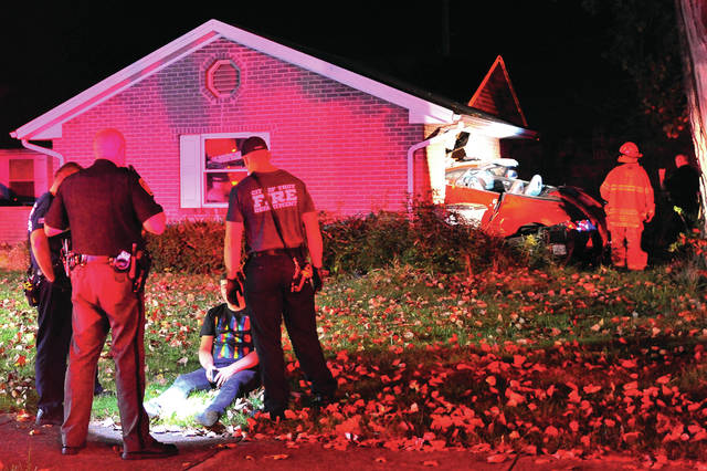 Mike Ullery | Daily Call Troy Fire Department medics check out the driver of a vehicle that crashed into a house on North Road, in Troy, on Sunday evening while firefighters and Troy police officers access the damage to the home.