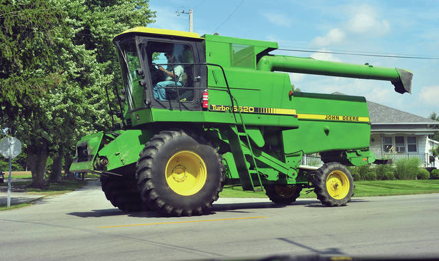 Mike Ullery | Daily Call A farmer drives his combine on US Rt. 36 at Mulberry Grove -Rakestraw Road on Friday. As fall harvest gets in to high gear, motorists are urged to use caution on the roadways as wide and slow-moving farm equipment will be frequent travelers in coming weeks.