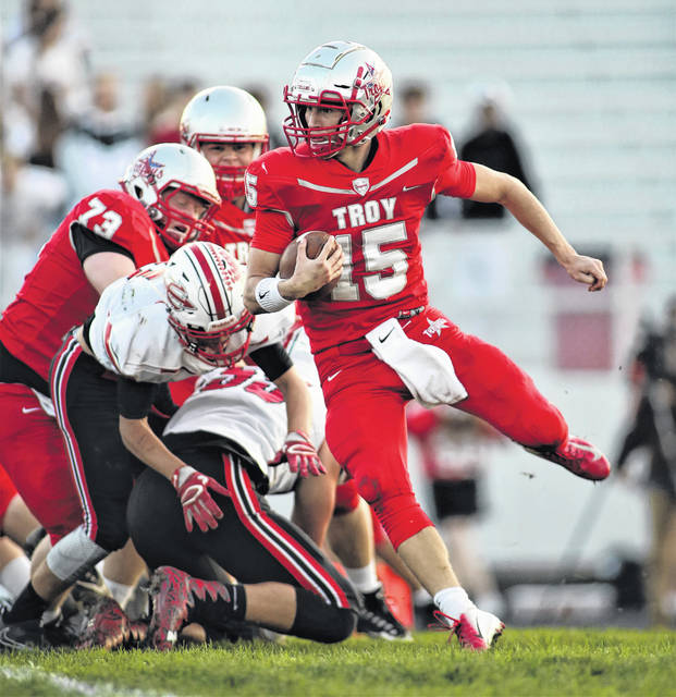 Lee Woolery | Troy Daily News Troy quarterback Brayden Siler (15) slips a tackle against Tippecanoe Friday.