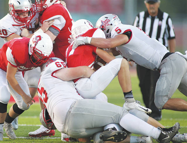 Lee Woolery | Troy Daily News Troy's Jakob Moorman (65) and Sam Jackson (5) tackle a Stebbins player last Friday. Moorman is one of four Troy sophomores seeing significant playing time this season.
