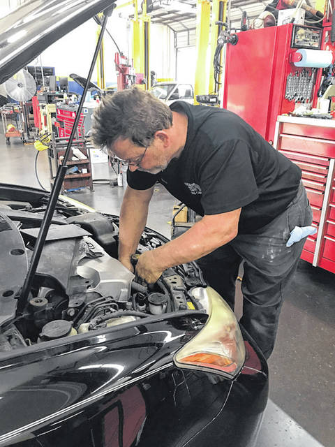 Melody Vallieu | AIM Media Midwest Scott Chaney works on a vehicle at Trojan Auto Care in Troy. Chaney recently was a finalist for the 2018 Auto Technician of the Year honor.
