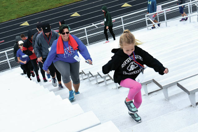 Cody Willoughby | Troy Daily News Ellie Campbell, 6, of Piqua leads a parade of participants up the bleachers during the Freedom Climb on Sunday at Troy Memorial Stadium.