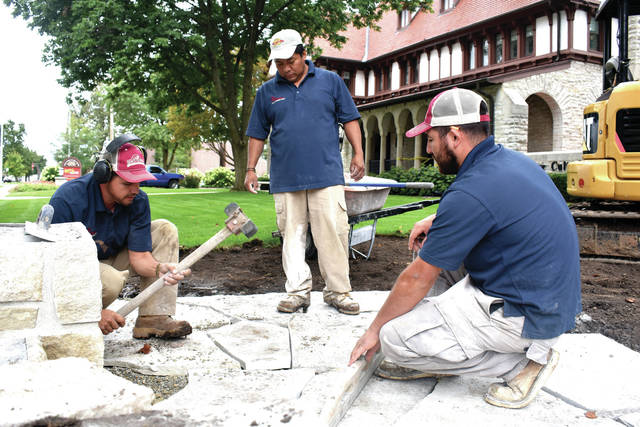Cody Willoughby | Troy Daily News From left, Herberto Olivares, Gabriel Senici, and Julio Perez of Fullmer's Artist and Landscape Design in Dayton lay limestone pavers at the southeast corner of the property at Troy-Hayner Cultural Center on Wednesday. The rejuvenation project underway at the center features a limestone wall and pavers at the southeast corner, along with new signage and a lamppost. In the building's rear, a paved walkway has been laid connecting the parking lot to Oxford Street. Two pads have also been laid for a picnic area and a bicycle rack, which was custom-made by Carole Kerber of Kerber Sheet Metal. Several new signs will be installed in the coming weeks. The project is expected to be completed by Wednesday, Oct. 31.