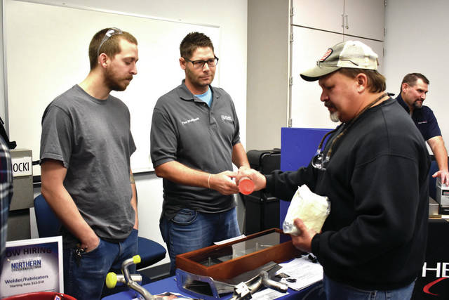 Cody Willoughby | Troy Daily News Eric Stelmat and Karl Sagowitz of GE Aerospace in Beavercreek share a tube of stainless-steel filawire with Kevin Scott of Troy during a skilled trade job fair at Hobart Institute for Welding Technology on Tuesday.