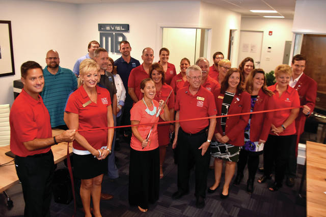 Cody Willoughby | Troy Daily News The staff of Level MB and members of the Troy Chamber of Commerce commemorate the firm's new location at 210 South Market Street on Thursday in Troy.