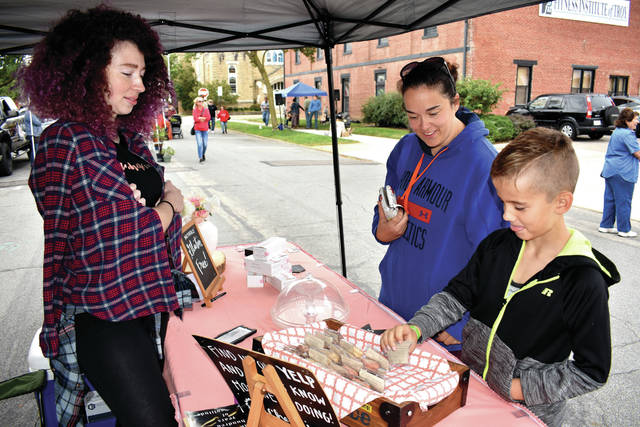 Cody Willoughby | Troy Daily News Michelle's Macarons vendor Michelle Adams transacts with and Tashina and Bennett Cromes of Troy during the Downtown Troy Farmers Market on Saturday.