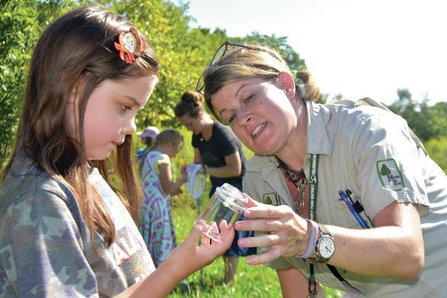 Cody Willoughby | Troy Daily News Adaline Erwin, 6, of Vandalia and Miami County Parks naturalist Raptor Rachel observe a captured moth during the Homeschool Nature Quest program on Tuesday at Lost Creek Reserve. The ongoing program encourages pre-registered homeschooled students and their families to increase time spent exploring the outdoors. Participating kids are able to check out a backpack filled with books and exploration tools to take home and continue the fun. For more information, visit www.miamicountyparks.com, or find Miami County Parks District on Facebook.