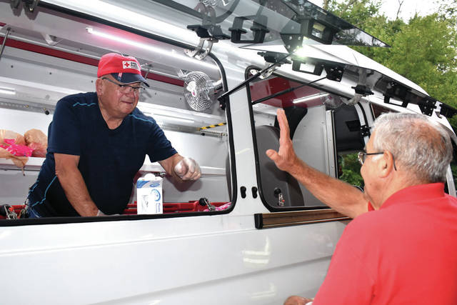 Cody Willoughby | Troy Daily News Northern Miami Valley Ohio American Red Cross volunteer Ray Smith serves ice cream to volunteer John Gross out of the new Emergency Response Vehicle during its official unveiling at the NVMO Chapter on Monday in Troy.