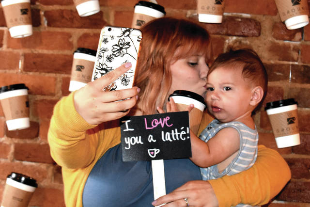 "Cody Willoughby | Troy Daily News Janna Grant of West Milton gives a smooch to Judah, 8 months, at the customized selfie station inside Grounds for Pleasure during ""See Yourself in Tipp,"" a special event hosted by Downtown Tipp City on Friday."