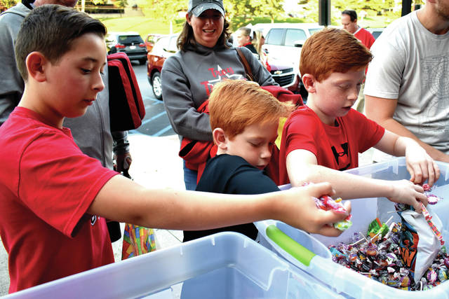 Cody Willoughby | Troy Daily News Connor, 11, Chance, 7, and Casey Haywood, 9, of Troy, engage in speed volunteering at the Isaiah's Place booth during Troy Main Street's Summer Sendoff event at on Friday at Troy Memorial Stadium.