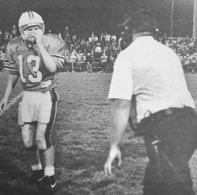 Troy Daily News file photo Former Tippecanoe quarterback Matt Burgbacher (left) gets instructions from his father, former Tippecanoe coach Charlie Burgbacher, during a 1993 game. Matt Burgbacher is now the head coach at Troy, while Charlie is Troy's defensive coordinator. Troy and Tippecanoe will play Friday at Troy Memorial Stadium.