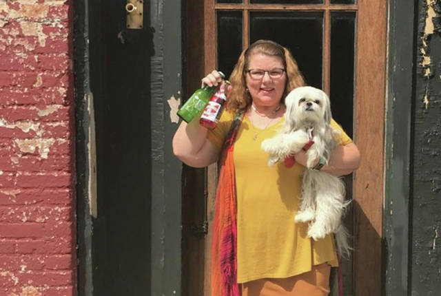 Provided photo Barbara Cooper and her dog Bailey show off some of the craft sodas that will be available at Connections of Tipp City, a new place for teens to hang out after school on Fridays at 35 E. Main St. in Tipp City.