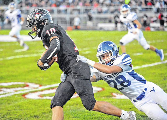 Josh Brown | Troy Daily News Covington's Andrew Cates carries the football after a reception as Miami East's Nick LeValley attempts to bring him down during a game earlier this season. Both Covington and Miami East are in the hunt for playoff spots.