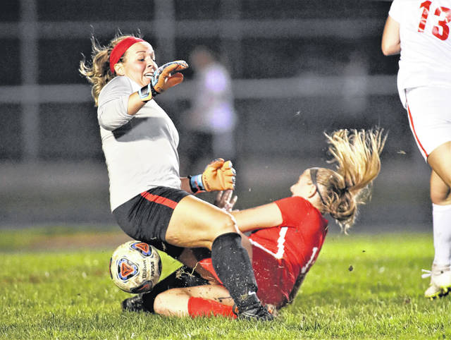 Lee Woolery|Troy Daily News Tippecanoe goalkeeper Lauren Robbins and Troy's Chamber Browning collide during Wednesday night's game at Troy Memorial Stadium.