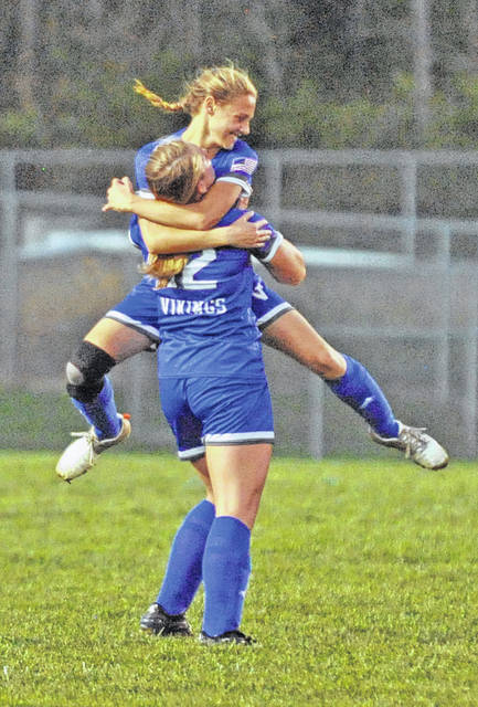 Josh Brown|Troy Daily News Miami East's Paxton Hunley jumps into the arms of teammate Whitley Gross (12) after scoring the first goal Monday night against Bethel. Gross had the assist on the play.
