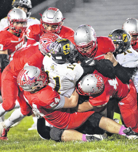 Lee Woolery|Troy Daily News The Troy defense smothers a Sidney ballcarrier Friday at Troy Memorial Stadium.
