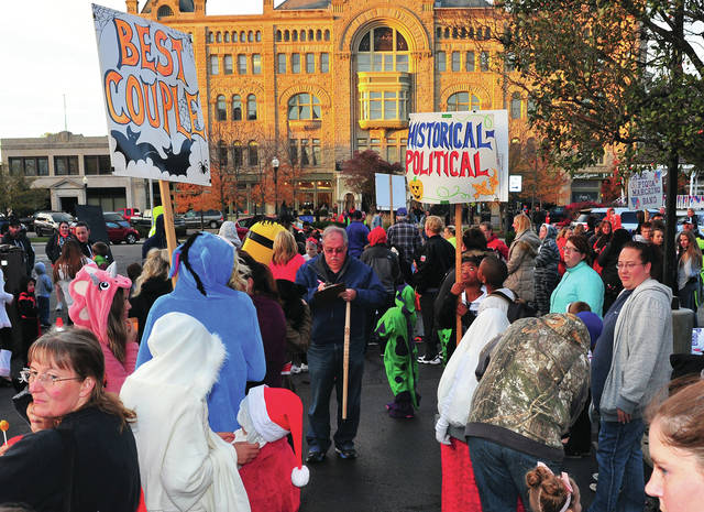 Mike Ullery | AIM Media Midwest Kiwanis Halloween Parade Chairman Mark Wion, center, separates the ghosts from the goblins as he organizes the annual children's Halloween Parade and Costume contest in downtown Piqua in 2017. The parade has been held annually since 1954.