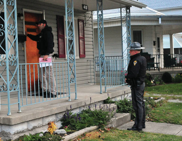 Detective Miles Gearing of the Piqua Police Department and Trooper Jordan Monnin from the Piqua Post of the Ohio State Highway Patrol check a residence in Piqua to verify the residency of a Miami County registered sex offender early Thursday morning.