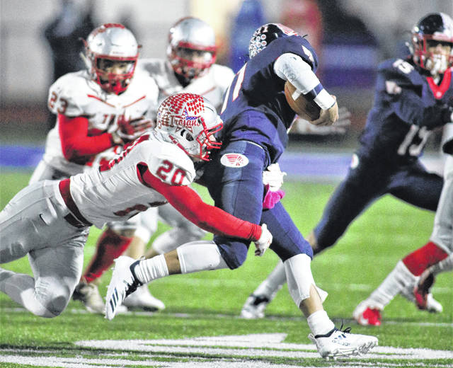 Lee Woolery|Troy Daily News Troy's Blake Burton (20) tackles Piqua's Micah Karn Friday.