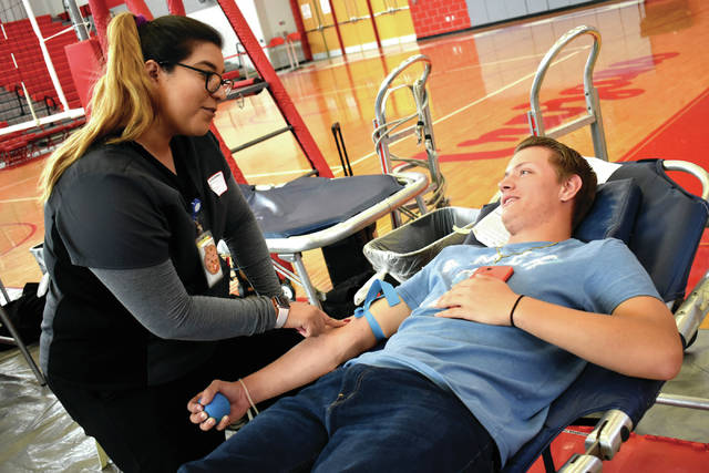 Cody Willoughby | Troy Daily News Blood donation specialist Karina Carrozza prepares Troy High School senior Wyatt Centliver for a blood donation during the 21st annual Troy-Piqua Challenge Blood Drive on Tuesday at Troy High School.