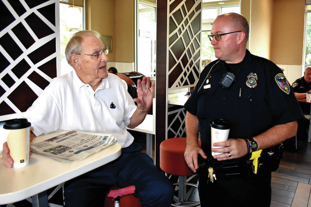 Cody Willoughby | Troy Daily News Charles Walton of Troy chats with patrolman Tracy Long during National Coffee with a Cop Day on Wednesday, hosted by Scott Family McDonald's in Troy.