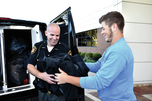 Cody Willoughby | AIM Media Midwest Skills USA member Andrew Fogt (right) hands off the last two of 947 donated coats to UVCC school resource officer Phil Osting during a pick-up by deputy sheriffs at Upper Valley Career Center on Thursday.