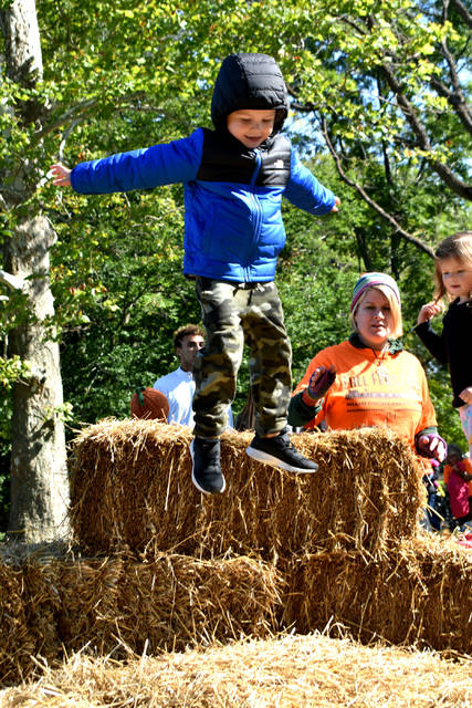 Cody Willoughby | AIM Media Midwest Alec Foster, 4, of Tipp City takes a leap into the hay during Fall Farm Fest on Saturday, Oct. 13 at Lost Creek Reserve.