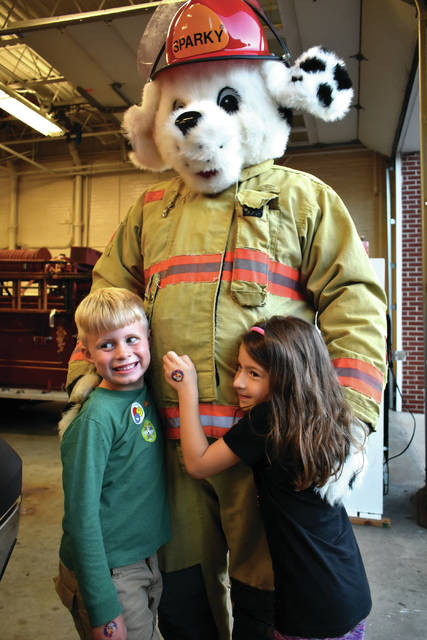 Cody Willoughby | Troy Daily News Noah Barnes and Katerina Sciortino, 6, of Tipp City meet Sparky the Fire Dog during a visit with firefighters on Tuesday in Tipp City. The event was organized as part of Fire Prevention Week 2018, which runs Oct. 7-13.