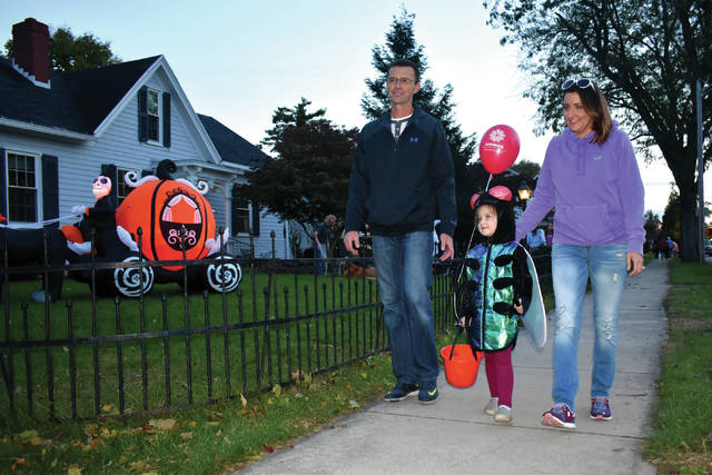"Cody Willoughby | Troy Daily News Kendall McDermitt, 4, of Troy walks up South Plum Street as a housefly with parents Dan and Tayla during ""Trick-or-Treat"" on Tuesday in Troy."