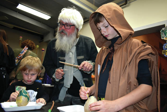 Cody Willoughby | Troy Daily News Tim Wells, as Timbelledore, assists Terence Davy, 5, of Dayton, and Matthew Waller, 10, of Troy in the painting of dragon eggs during the 6th annual Hallowizard Weekends on Friday at Mayflower Arts Center. The immersive experience encourages attendees to adorn Hogwarts-style costumes as they are led through an interactive sorting ceremony, a Quidditch tournament, potion and spells classes, and arts and crafts projects revolving around wizard wands, dragon eggs, remembrall charms, and more. For more information, visit www.mayflowerartscenter.com.