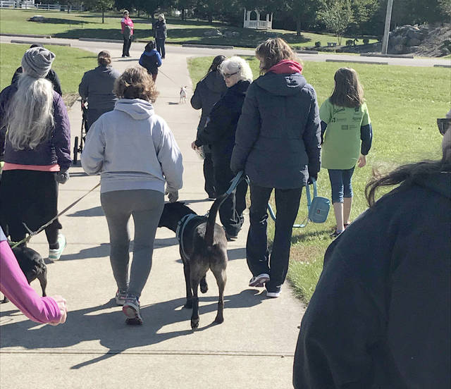 Melody Vallieu | AIM Media Local residents and their canine companions begin the Ohio's Hospice of Miami County 2018 Remembrance Walk at Duke Park on Sunday. The walk was a fundraiser to raise funds for the organization and for those who lost a loved one during the year to honor them.