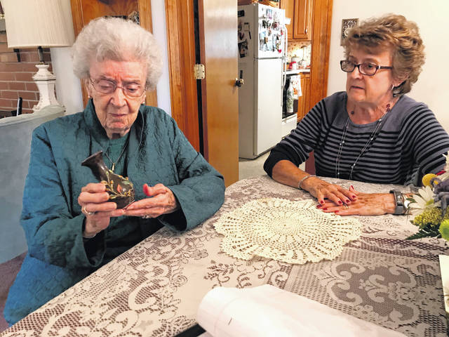 Melody Vallieu | AIM Media Midwest Dorothy Laufer, left, who will turn 100 years old, reminisces about a small vase she was awarded in a county fair in her childhood. The vase has been a treasured item of Laufers throughout her lifetime.