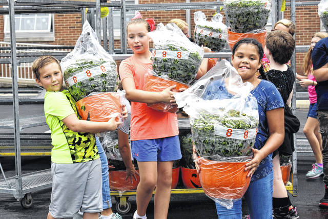 Cody Willoughby | Troy Daily News Fifth grade student coucil members Alex McAdams, Riley Maurer, and Vivian Walker help unload mumkins during a delivery on Tuesday at Forest Elementary School.