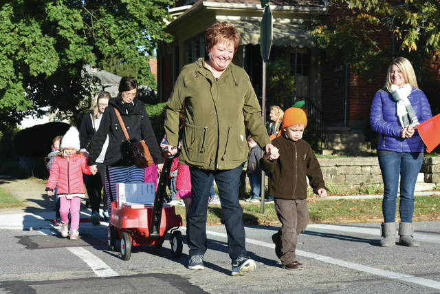 Cody Willoughby | Troy Daily News Teacher Linda Godfrey and preschooler Lliam Saltis lead a group of students and volunteers from First Kids Christian Cooperative Preschool to the post office on Wednesday.