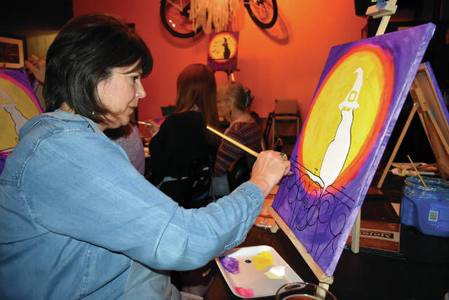 Cody Willoughby | Troy Daily News Carolyn Bilger, of Troy, paints a spooky Halloween scene during the Paint for Paws FUNdraiser event on Wednesday at Mojo's Bar and Grille. Under the guidance of Lisa Bauer of the Mayflower Arts Center, participants were provided materials to create their own masterpiece on a 16x20 canvas. All proceeds from the event benefit Cat Advocates of Troy and its trap, neuter, and release program. For more information, visit Cat Advocates of Troy on Facebook.