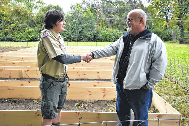 Cody Willoughby | Troy Daily News Cade Johnson, 17, of Troy shakes hands with gardener Niall Foster following the implementation of raised beds in the community garden at Lincoln Community Center.