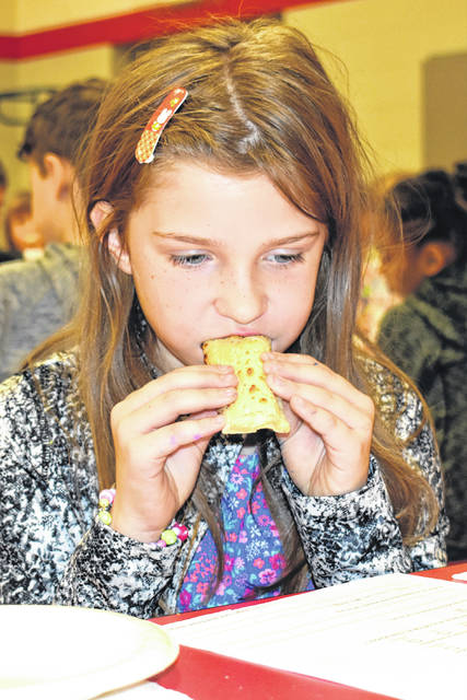 Cody Willoughby | Troy Daily News Fourth grader Brooklyn Maio samples a cheese-filled breadstick product during a taste test with Conagra Foods on Thursday at Hook Elementary School in Troy.