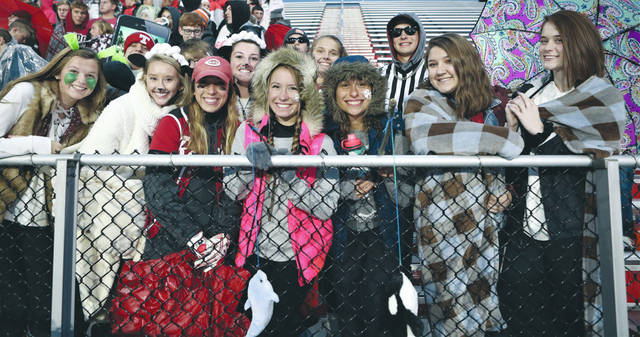 Lee Woolery | Troy Daily News Fans of the Troy Trojans brave the chilly, wet weather to cheer on their football team Friday night at Piqua's Alexander Stadium in the 134th meeting between the two schools.