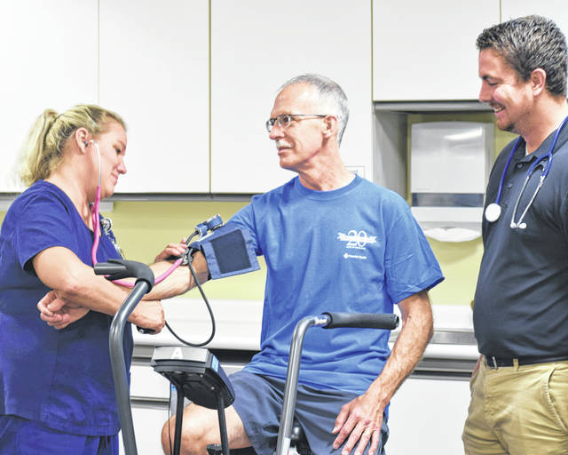 Provided photo Roger Ely, center, is checked by Theresa Rowley, RN, during a cardiac rehab visit at UVMC while Aaron Christy, right, looks on.