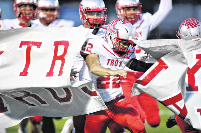 Lee Woolery | Miami Valley Sunday News file photo Led by senior Kobe Felnter, the Troy football team breaks through the banner prior to the Week 9 game against Greenville.